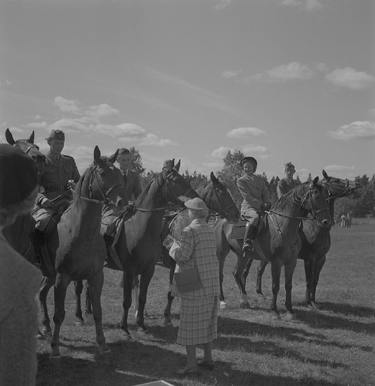 Ridningen 11 juni 1950. Prisutdelning efter ridtävlingen. En kvinnlig ryttare fårpris av en dam i rutig dräkt och hatt.