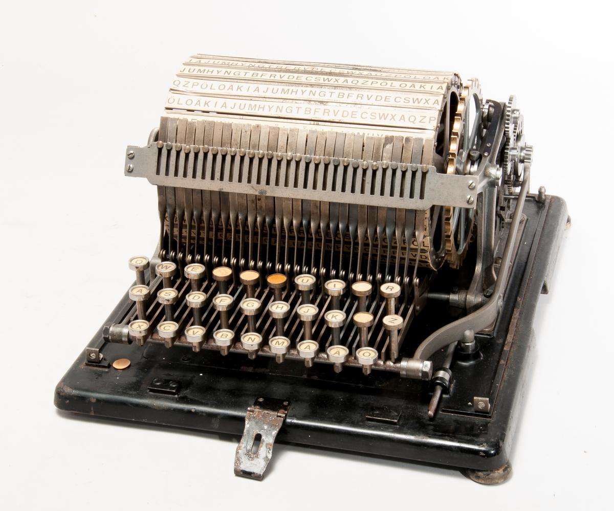 Maskin för kryptering. 1915. Maskinen kan göras kompatibel med objekt 27633. Chiffrering sker från ett oordnat fast alfabet mot ett oordnat alfabet på en trumma med plats för 29 alfabeten. Trumman roteras oregelbundet styrt av en kedja.  Lucka på huvens baksida saknas, bottenplattan spräckt.