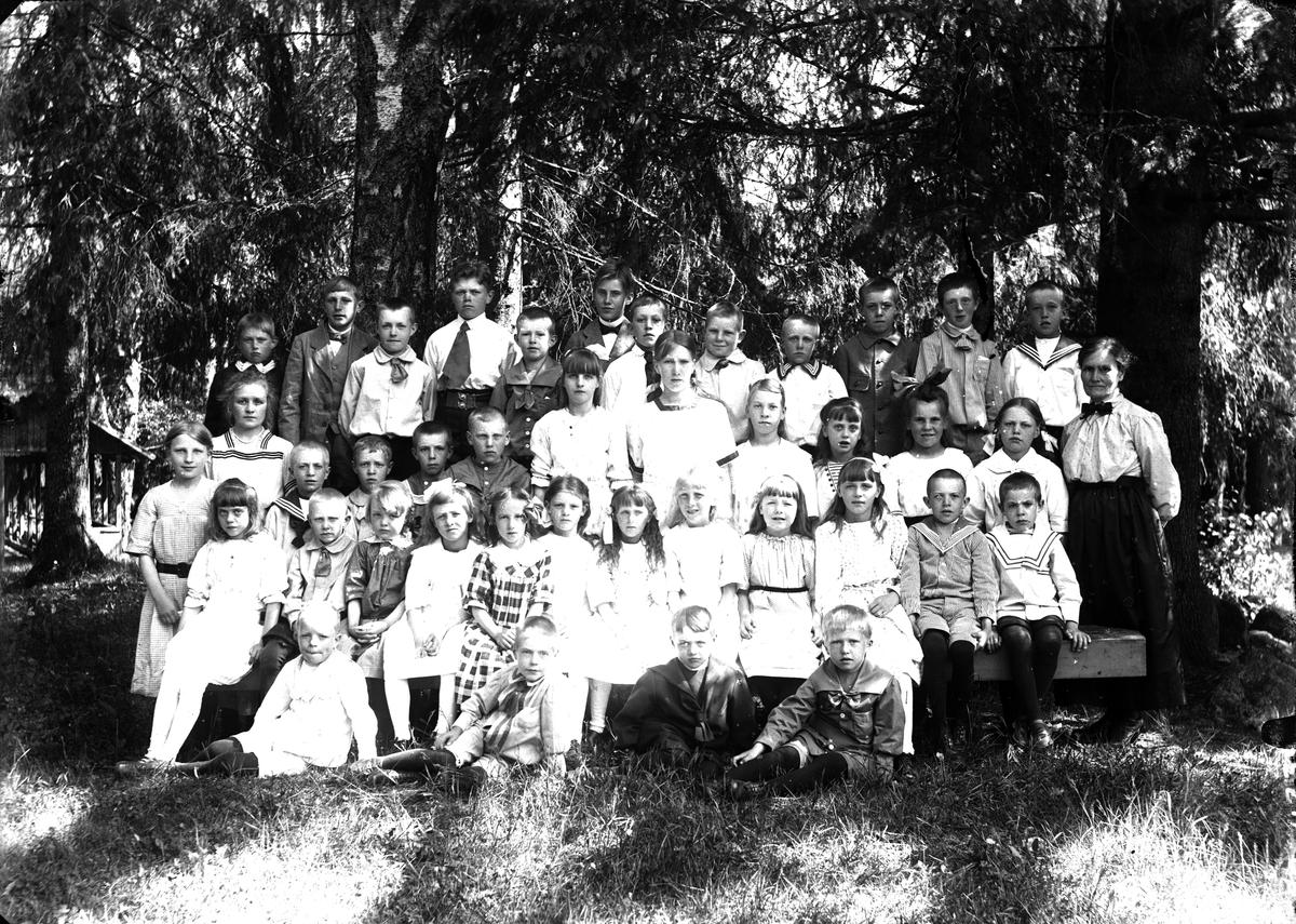Lärarinna med en samling skolelever i skogen.
