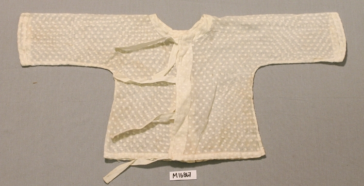 Barnskjorta av vitt bomullsvoile med  invävda prickar. Mitt fram längsgående veck. Öppen mitt bak, knytes med fyra par knytband (90 x 11 mm.) av bomull. Mått; L: 250 mm. Br: 540 mm (ärm-ärm), 250 mm (nedk).  Inskrivet i huvudbok 1961. Funktion: Barnskjorta