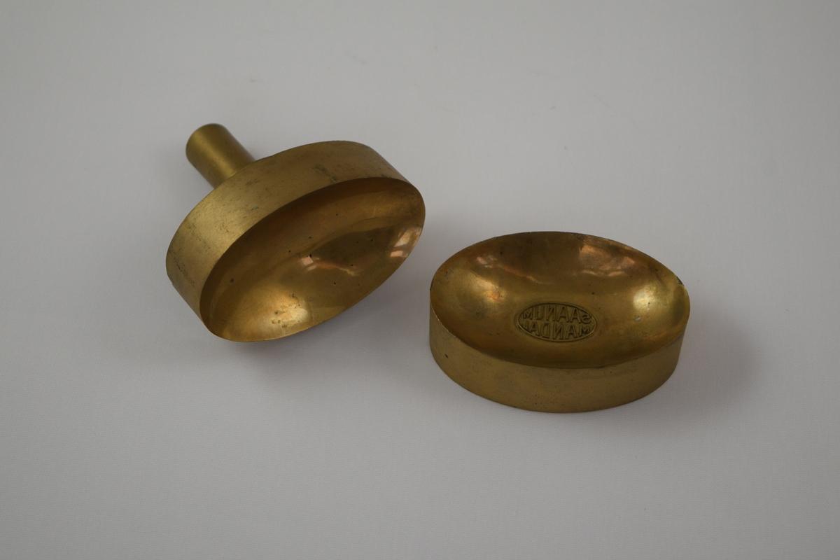 Oval såpeform i to deler for produksjon av såper ved Saanums Sepefabrikk AS i Mandal. Sannsynligvis jern med messing utenpå.  Konkav topp (A) og bunn (B) med relieff/motiv/tekst for trykk. Bare bunnen har motiv/tekst.
