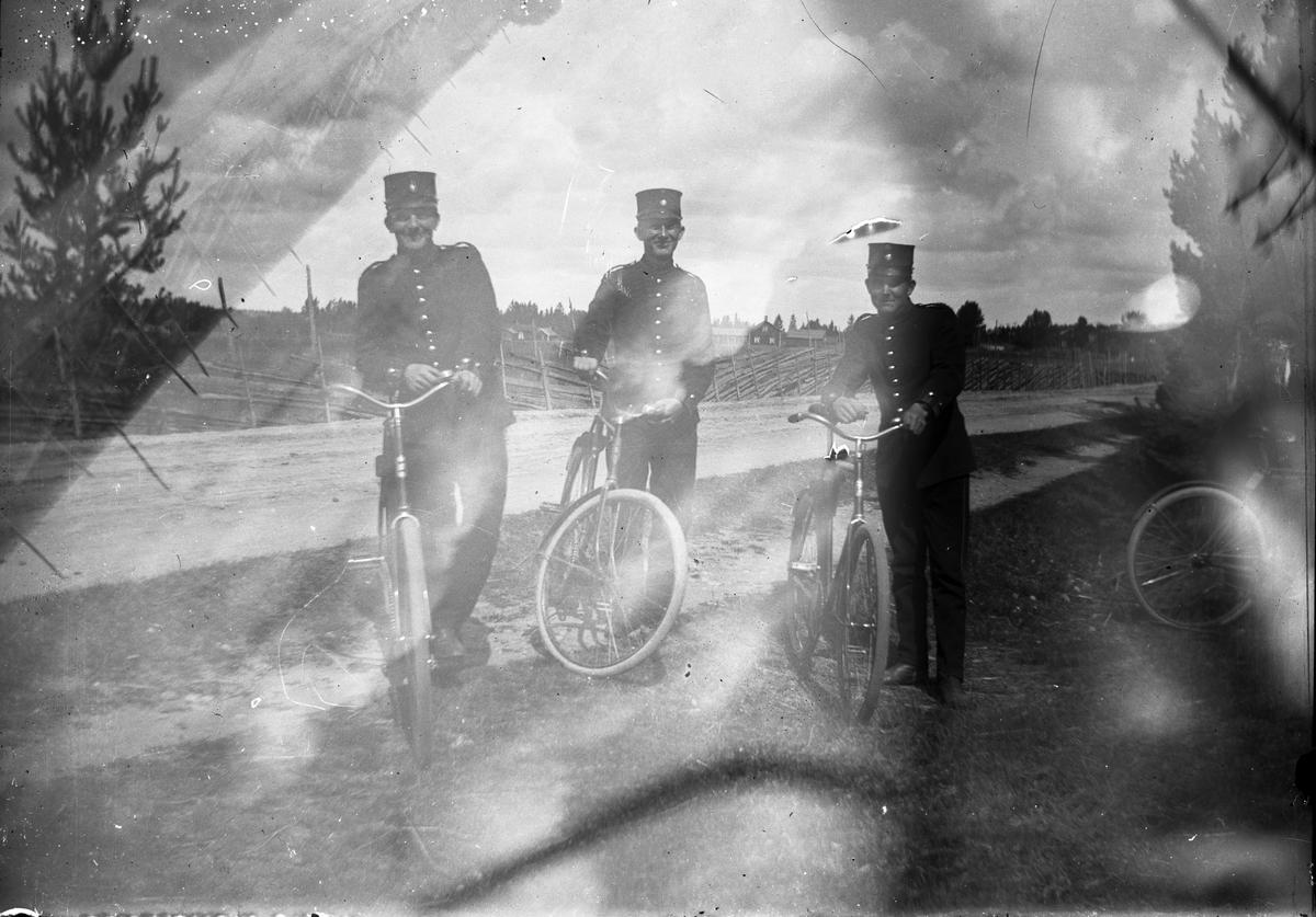 Tre män med cyklar.