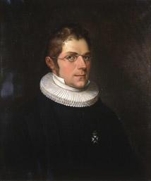 Portrett av Nicolai Wergeland. Kort hår, briller, presteklole og prestekrave. En orden.