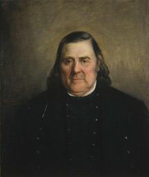 Portrett av Theis Lundegaard. Mørk drakt. Gyllenbrun bakgrunn.