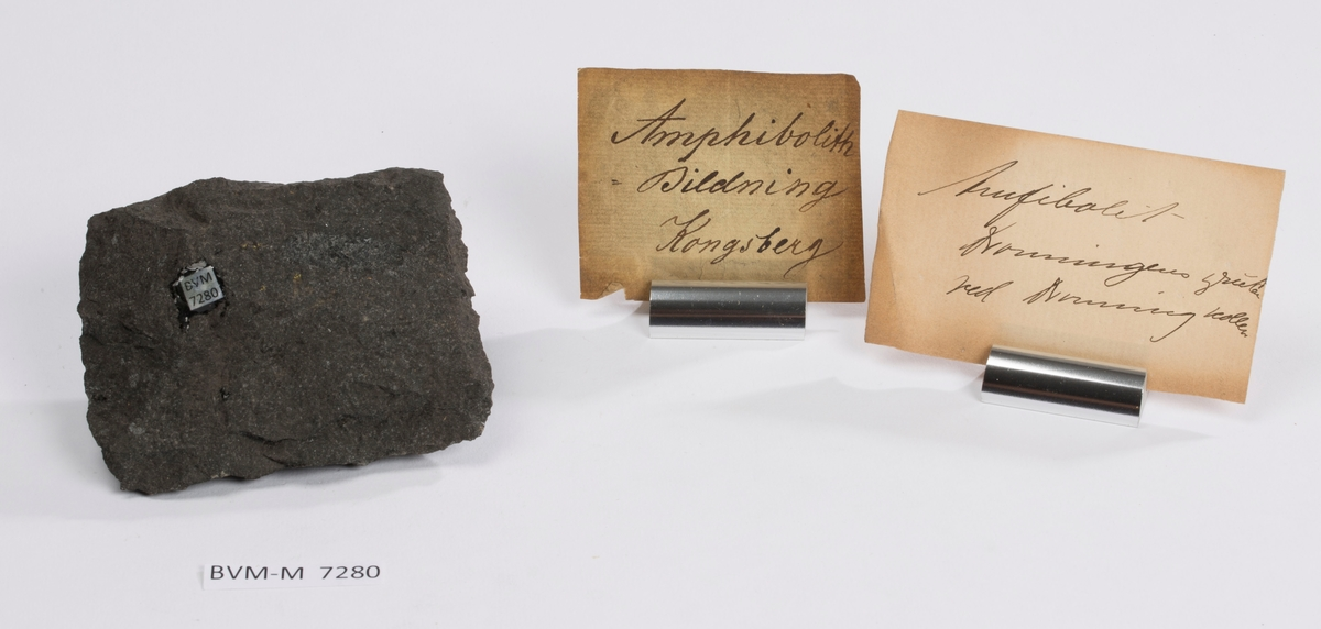 To etiketter i eske: Etikett 1: Amphibolith - Bildning Kongsberg  Etikett 2: Amfibolit Dronningens grube ved Dronningkollen