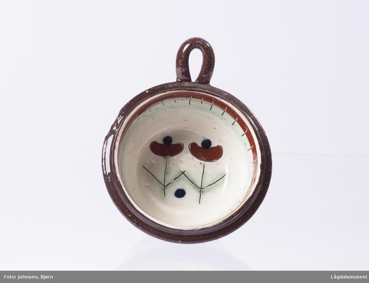 Kopp med dekorert innside. Dekoren er to blomster i bunnen av koppen og et ornament dekorert rundt toppen av koppen (på innsiden). Hanken er utformet for å kunne henge opp koppen. Ornament på utsiden med en stripe hvitt (med litt blått i) med røde prikker.