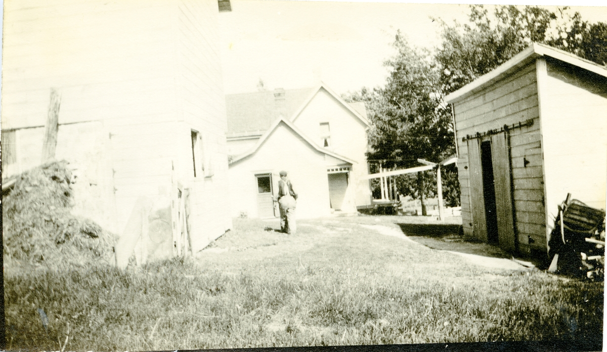 Bildet viser et tun med to hus og en garasje. En mann går over gresset mellom disse bygningene. I Amerika.