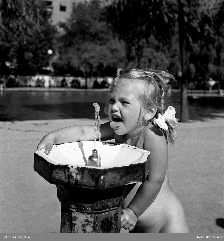 En flicka dricker från en vattenpost
