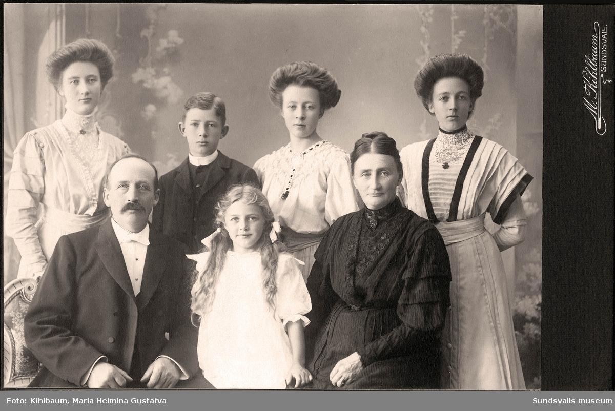 Ateljéporträtt på möbelsnickaremästaren Gustaf Hydén med frun, stadsbarnmorskan, Anna Hydén samt deras fem barn. Stående från vänster dottern Anna, sonen Gustaf, dottern Mary samt dottern Elin. Mittemellan föräldrarna sitter dottern Rut. Familjen var bosatt på Skepparegatan 12, Norrmalm, där fadern även hade sin snickeriverkstad.