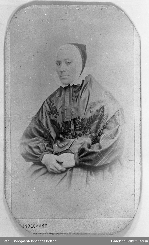 Portrett av Kari Olsdtr. Hoff f. 1822 d. 1898, sittende i rutet kjole, honnlue med skru og med silkesjal over skuldrene.