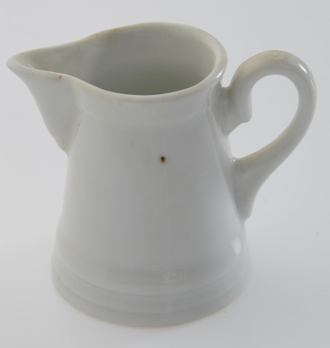Miniatyrfløtemugge  (en persons).   Porselen,  hvit glasur, ustemplet.    Skrå sider med profilring nede,  spiss tut og liten hank.