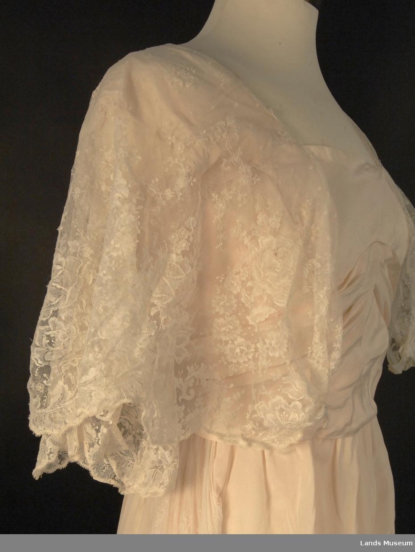 Maskinprod. tyllbroderi. Tyllermer, tyllkapper over skulderene og tyllvolanger i skjortesidene.