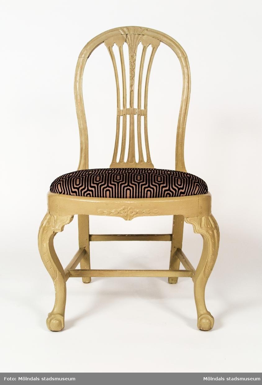 Axknippestol som kombinerar en gustaviansk rygg med ben utförda i rokoko. Stolen visar på ett intressant blandning där nya och gamla modeelement möts. Stolen är ej signerad men är utan tvivel tillverkad i Lindome.Stolen är ommålad 2002. Den grå färgen har lagts ovanpå den tidigare målningen, som var rosa och ljusblå och ornerad med guldfärg. Ommålningen har gjorts av Lars Olausson, möbelrenoverare.Stolen är inköpt år 2002 genom Per Falck, intendent vid Nordiska museet från antikhandlare Lars Broberg, Stockholm.