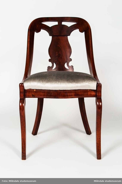 """Stol, s.k. """"Göteborgsstol"""", tillverkad i mahogny. Mjukt svängt rygg, genombruten ryggbricka. sabelformade framben. Lös stoppad rygg sits klädd med roströd plysch.Frambenens utformning tyder på att stolen är tillverkad under Karl-Johantidens senare del, dvs omkring 1840.Inköpt på Lilla Bukowskis, Stockholm.Samhör med MM02397"""