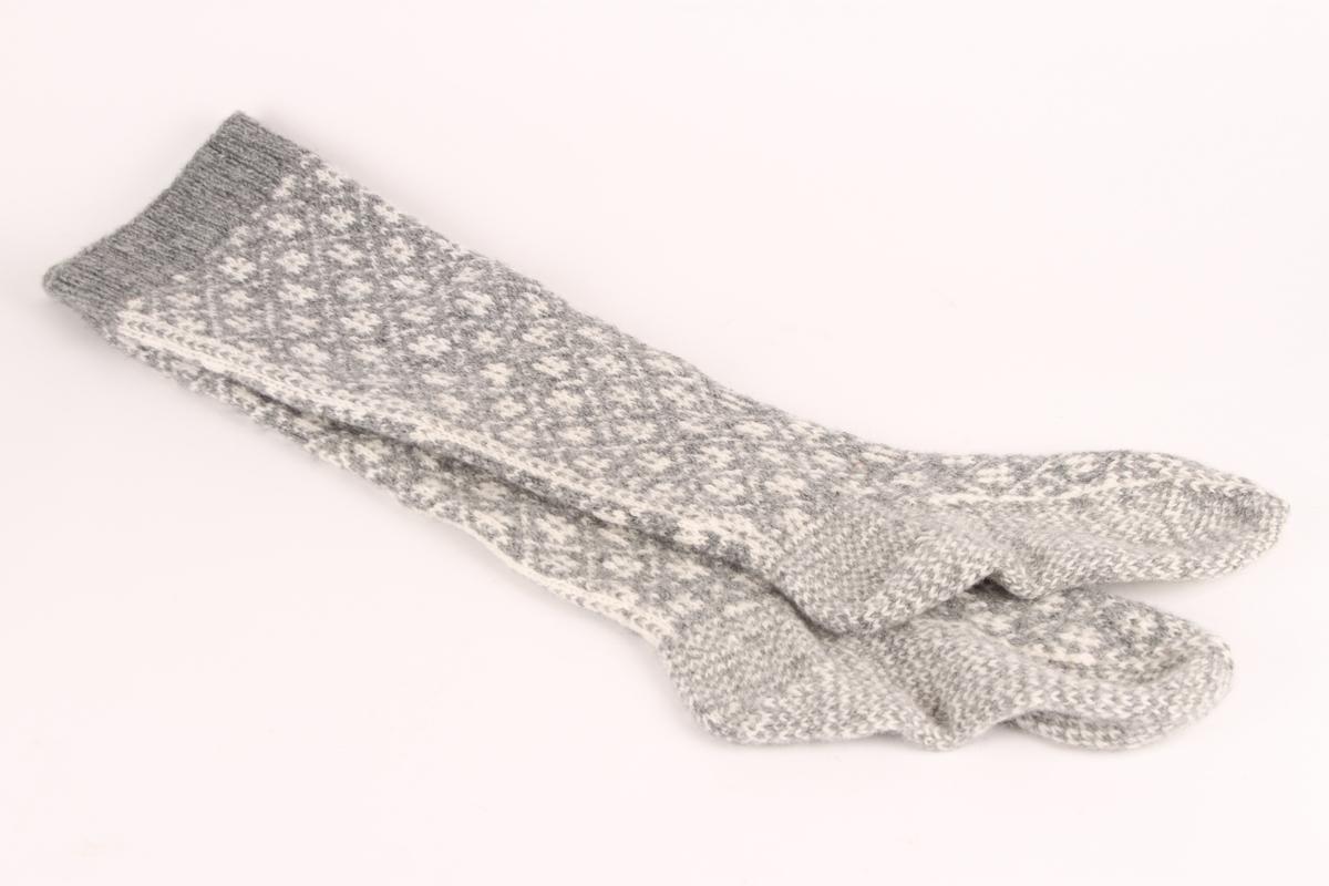 Et par selbustrømper i grått og hvitt, med grå vrangbord. Stolpe nedover leggen.