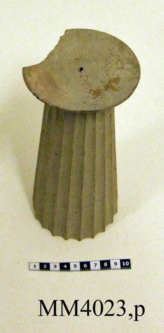 Pelare, eller kolonner, släta och räfflade (sju st halvkolonner, räfflade). 20 st. modeller av trä avsedda som fasadprydnader. Pelarna är räfflade med halvcirkelformig basyta. De är vitmålade. Kapitälen är av närmast dorisk stil. Pelarna utgör modeller till gavelkonstruktion för nya inventariekammaren på varvet 1785-87. De sammanhängs troligen med en serie av gavelmodeller och pelare som finns i kistan i sal 1 och vid norra delen av väggen i samma sal. (K 2244)  Kolonn, kannelerad med kapitäl och fast abakus. Målad i gråvitt.