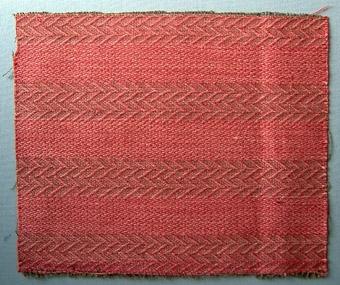 Vävprov, möbeltyg i bomull, ull och lin vävt i korskypert med inslagseffekt (kypert 3.1.1). Randigt, varannan rand är viggmönstrad. Varp i brunt bomullsgarn, nr 16/2. Varptrådarna löper två tillsammans.Inslag i rödrosa lingarn nr 16/1 och 16/2 och ullgarn; redgarn nr 20/2, tre trådar tillsammans per inslag. (Ev. vävt för firma Carl Malmsten?)