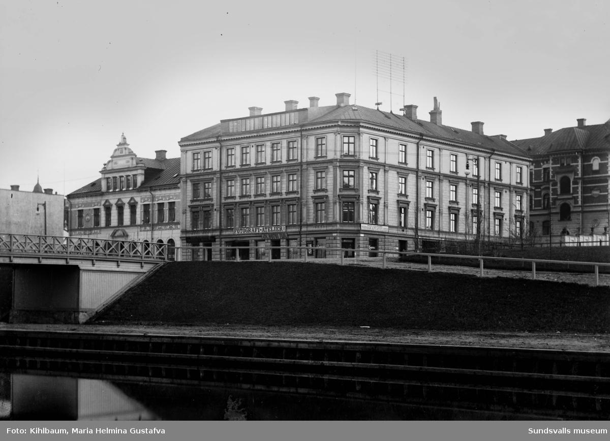 Hellbergska huset på Storgatan 33 där Maria Kihlbaum hade sin fotoateljé. Skyltarna kan ses på gatuplanet. Huset byggdes några år före den stora stadsbranden 1888 men klarade sig skapligt p g a av att den var byggd i sten. Den reparerades och revs först 1947. När Maria flyttade in 1897(där hon hade även sin bostad) fanns bara torrklosett och kallt vatten i kranarna. Man eldade då i vedspisar och kakelugnar. Längst upp ses takfönstren till hennes ateljé.