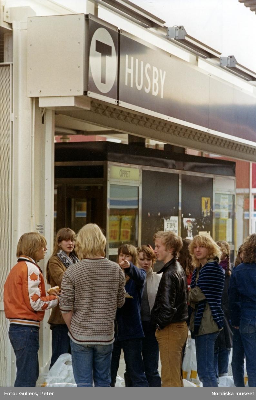En grupp ungdomar står utanför tunnelbanestationen i stockholmsförorten Husby.
