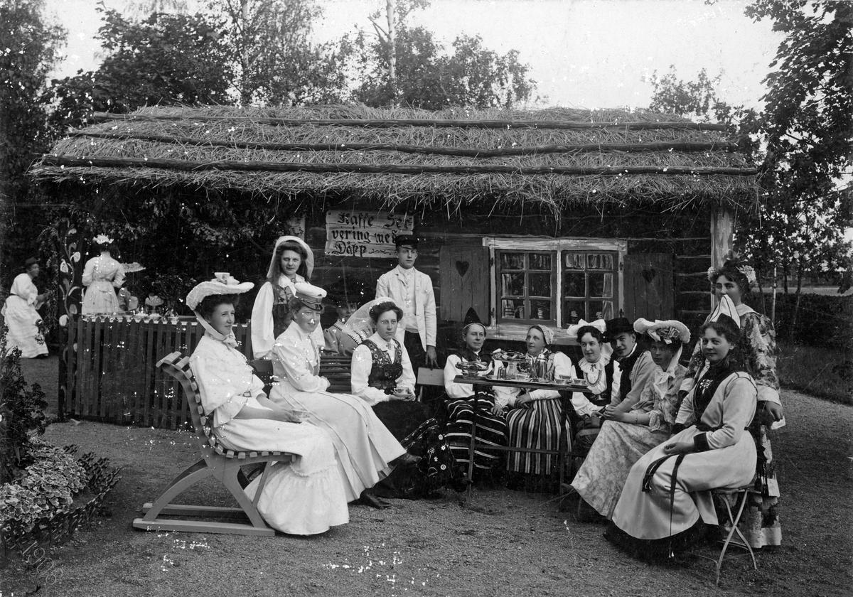 """Kaffeservering på Alphyddan, 1906. Damer dricker kaffe. Litet hus med halmtak med skylten Kaffeservering med dåpp"""".  Köpings spritbolags sommarschweizeri, Alphyddan."""