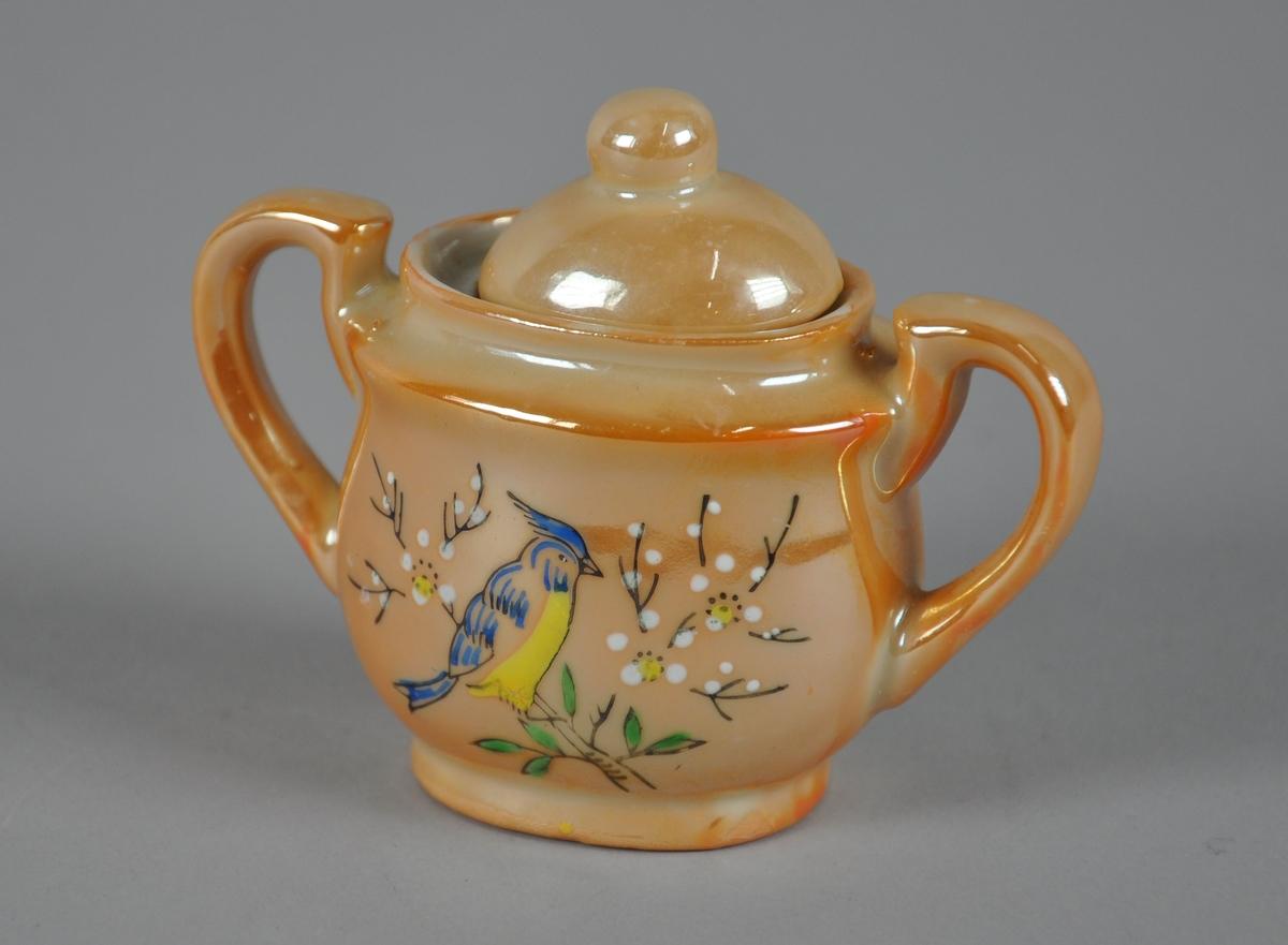 Liten sukkerskål med lokk og to hanker. Kannen har gullfarge og malt dekor midt på korpus med motiv av fugl i tre.
