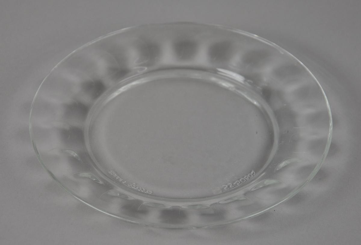 Asjett av glass med opphøyd kant. Fasettert mønster på kanten av asjetten,