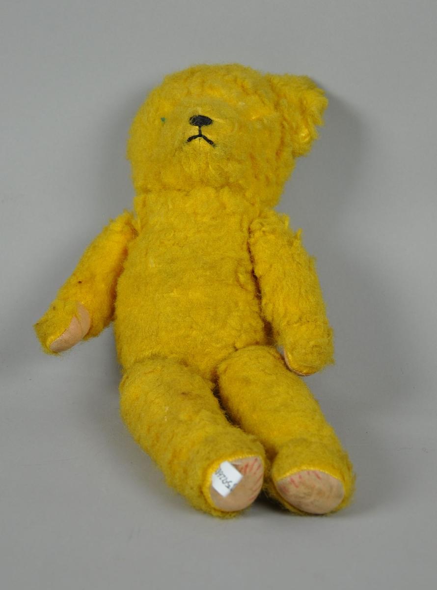 Gul teddybjørn. Den mangler et øre og et øye.