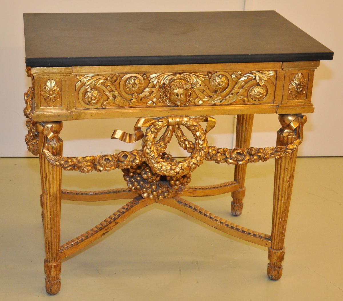 Bordet er av forgylt tre med toppplate av stein. Bordet er riklig utskåret. Bordet er i fransk ny-klassisisme, nærmere bestemt Louis XVI.