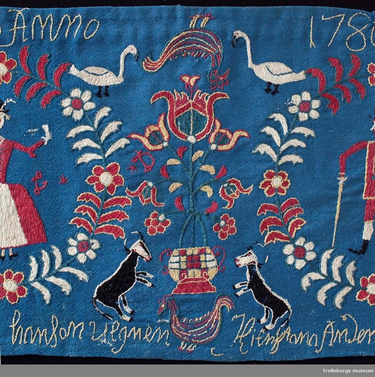 På en mellanblå botten är två kransar broderade, i den ena kransen står en kvinna och i den andra en man. I dynans hörn är blommor broderade, samma blomma kommer igen i dynans mitt tillsammans med en tupp, två gäss och två kor. Broderiets färger är rött, vitt, gult, grönt och svart. Dynan är märkt Anno 1780 Nils Hansson Ulgren Kierstin Andersdotter.