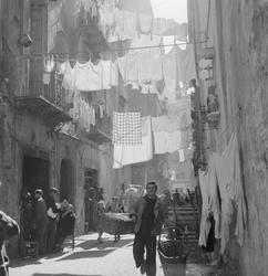 Gata i Neapel med folkvimmel och upphängd tvätt mellan husen