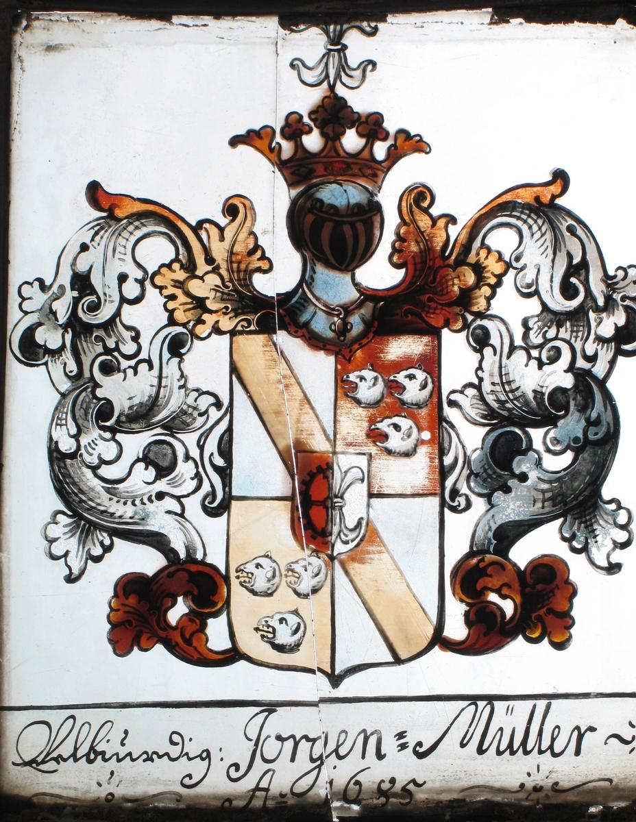 Våpenskjold i hvitt og rødbrunt, med ranke og kronet hjelm  i grått/blått og brunt. Tekst under: Jørgen:  Müller: Ao 1685.