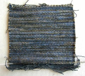 Vävprov, möbeltyg i bomull, lin och ull vävt i korskypert med inslagseffekt. Melerat i blått, grått och svart. Varp i svart bomullsgarn nr 16/2. Inslag i blått och grått lingarn nr 16/1 och 16/2 samt svart 1-trådigt ullgarn; möbeltygsgarn. Tre trådar tillsammans per inslag.