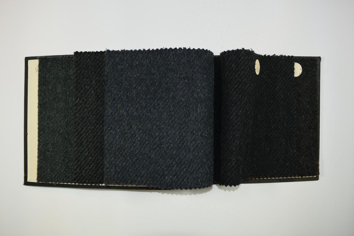 Prøvebok med 5 stoffprøver. Tykke ensfargede stoff, noen med skrå stiper i sort eller brunt. Stoffene ligger brettet dobbelt slik at vranga dekkes. Stoffene er merket med en rund papirlapp, festet til stoffet med metallstift, hvor nummer er påført for hånd. Innskriften på innsiden av forsideomslaget indikerer at alle stoffene i boken har kvalitetsnummer 90.   Stoff nr.: 90/9, 90/10, 90/11, 90/12, 90/13.