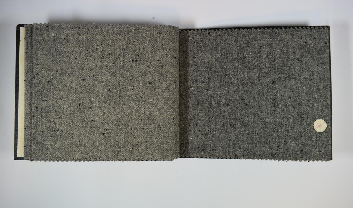 Prøvebok med 6 stoffprøver. Middels tykke stoff med tilsynelatende tilfeldigplasserte prikker. Stoffene ligger brettet dobbelt i boken slik at vranga dekkes. Stoffene er merket med en rund papirlapp, festet til stoffet med metallstift, hvor nummer er påført for hånd. Innskriften på innsiden av forsideomslaget indikerer at alle stoffene har kvalitetsnummer 140.  Stoff nr.: 140/31, 140/32, 140/33, 140/34, 140/35, 140/36.