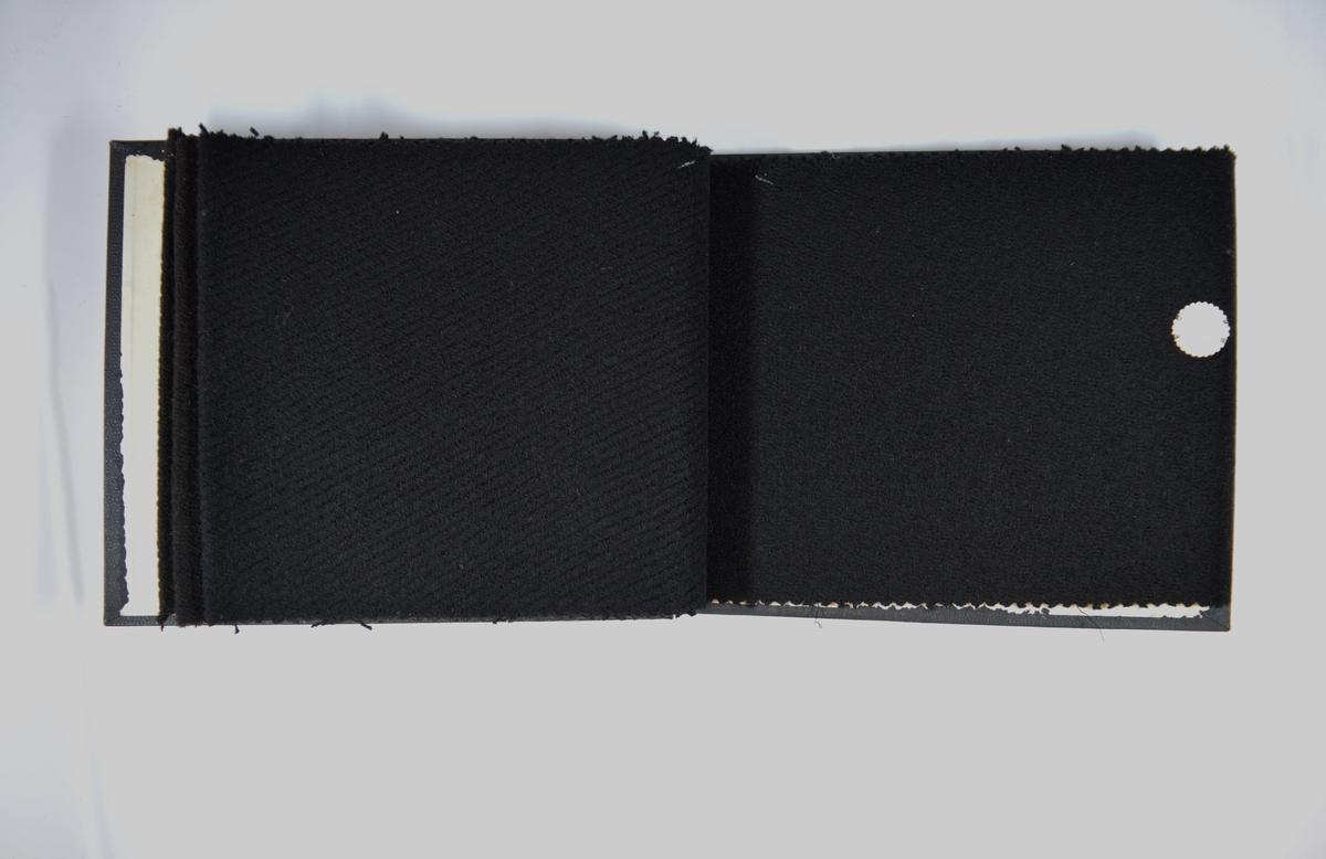Prøvebok med 4 stoffprøver. Middels tykke ensfargede stoff med diskret vevmønster av ulike slag. Stoffene ligger brettet dobbelt i boken slik at vranga dekkes. Stoffene er merket med en rund papirlapp, festet til stoffet med metallstift, hvor nummer er påført for hånd. Innskriften på innsiden av forsideomslaget indikerer at alle stoffene har kvalitetsnummer 112.   Stoff nr.: 112/5, 112/6, 112/7. 112/8.