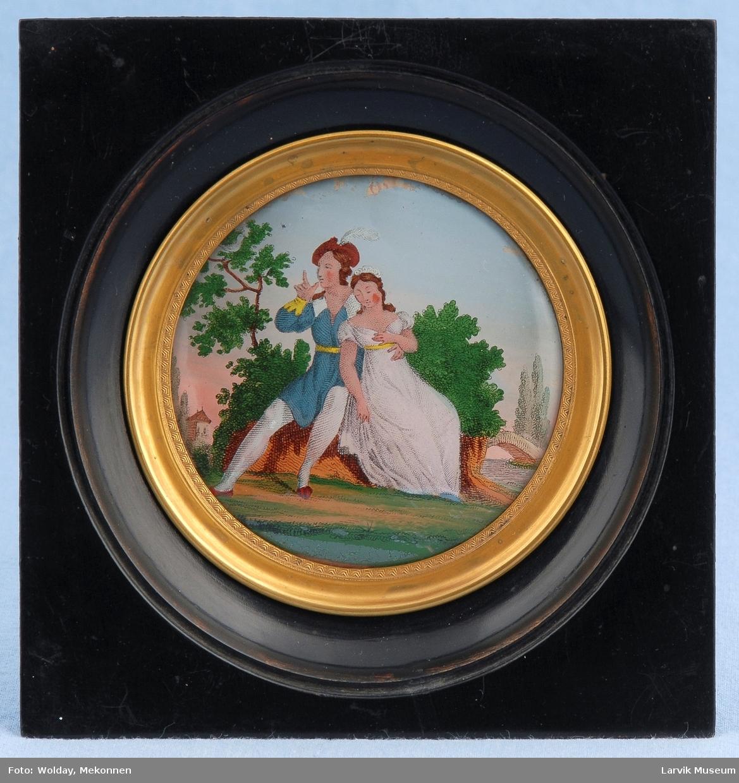 Et ungt par sitter på en stubbe, elv og trær i bakgrunnen. Romantisk.
