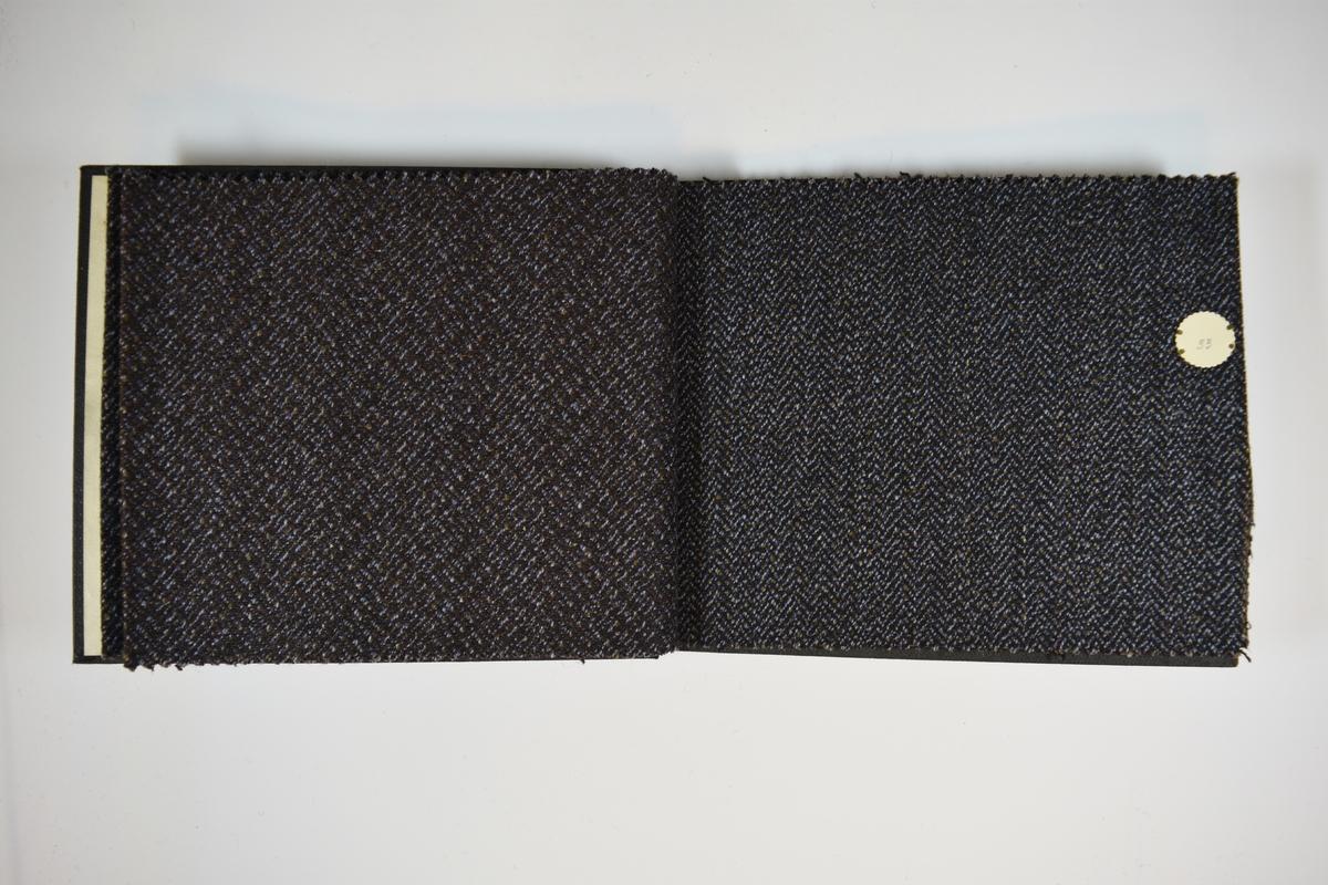 Prøvebok med 5 stoffprøver. Middels tykke stoff med fiskebensmønster eller lignende. Stoffene ligger brettet dobbelt i boken slik at vranga dekkes. Stoffene er merket med en rund papirlapp, festet til stoffet med metallstifter, hvor nummer er påført for hånd. Innskriften på innsiden av forsideomslaget indikerer at alle stoffene har kvaliteten 175.   Stoff nr.: 172/31, 175/32, 175/33, 175/34, 175/35.