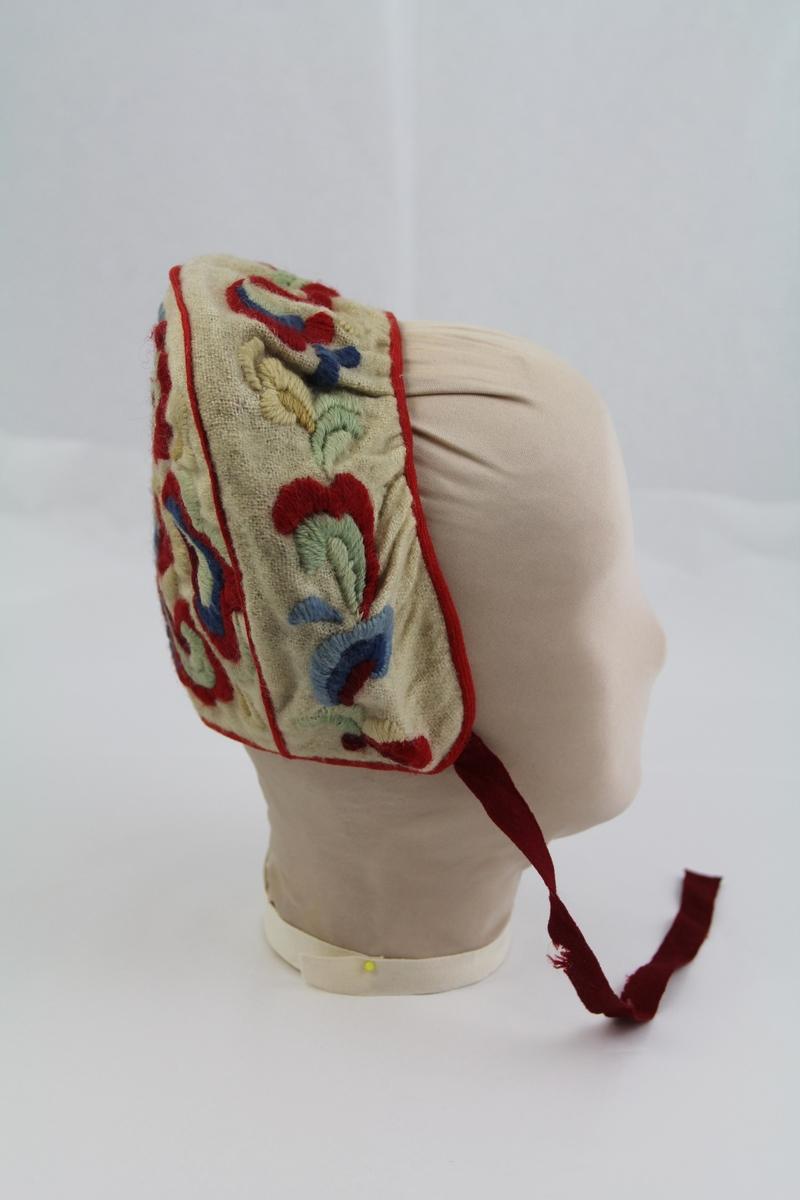 Kyse med brodert mønster. Hvitt ytterstoff, antagelig ull, for av tynnere hvitt stoff. Rødt bånd langs kyens kant, og to røde snorer til knyting unde haken. Mønsteret er roser eller andre tradisjonelle blomsterlignende ornamenter. Kysen og mønsteret har likheter med folkedrakter fra Hallingdal, kvinnebunad fra Hallingdal og Hulda Garborgs drakt.