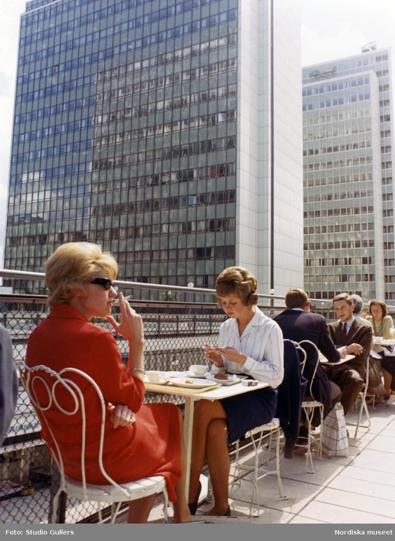 Stockholm. Cafégäster sitter vid bord på en uteservering. Hötorgsskraporna i bakgrunden.