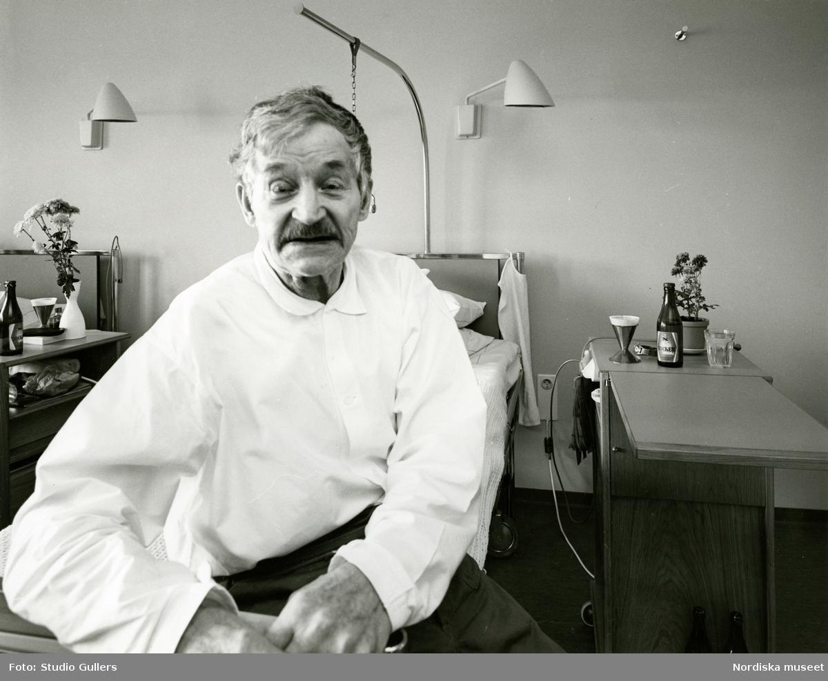 En äldre man sitter på en säng i en sal på ett vårdhem i Ånge. Bilden tagen på uppdrag av arkitekt Ervin Pütsep.