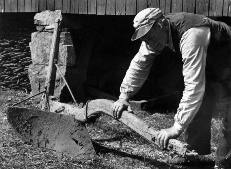 Alfred Iversen demonstrerer hvordan en måtte holde på plogåsen for å holde plogen nede i jorden, mens en annen gikk bak og holdt i styret. Ullbråtan, Bærum i Akershus, 1960.