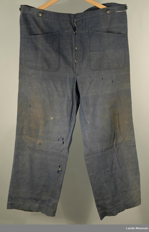 Mørkeblå dongribukse med knapper for bukseseler. Spensel bak med spenne. 2 utenpålommer foran, 16, 5 x 17,5 cm høge. 1 baklomme 17 cm x 17,5.