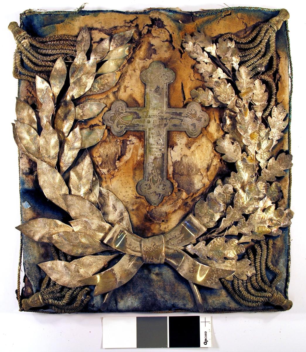 Kors omgitt av krans av blader i relieff.