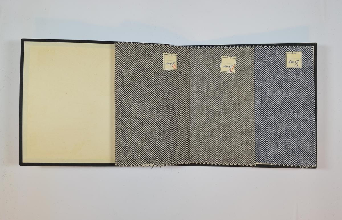 Rektangulær prøvebok med tre stoffprøver og harde permer. Permene er laget av hard kartong og er trukket med sort tynn tekstil. Boken inneholder relativt tynne, tette stoff med fiskebenmønster. Kyperbinding. Stoffene har ulike farger, men alle i kombinasjon med hvit/ufarget tråd. Stoffene er merket med en firkantet papirlapp, festet til stoffet med metallstifter, hvor nummer er påført for hånd.   Stoff nr.: 2005/1, 2005/2, 2005/3.