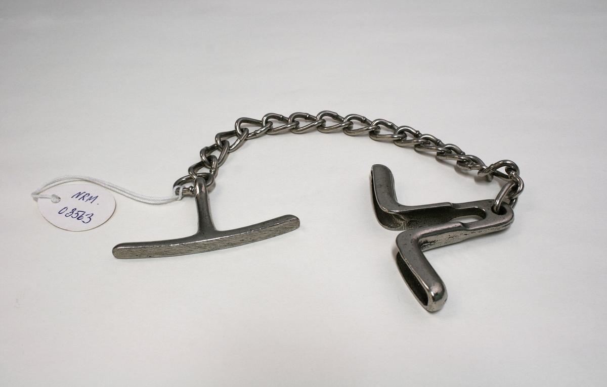 Håndjern av stålkjetting. Det er laget for å vris rundt så kjettingen setter håndleddet i klem og fremkaller smerte.