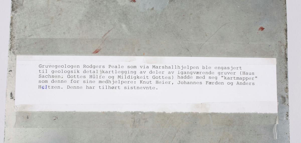 """Gruvegeologen Rodgers Peale, som via Marshallhjelpen ble engasjert til geologisk detaljkartlegging av deler av ignagværende gruver (Haus Sachsen, Gottes HÜlffe og Mildigkeit Gottes) hadde med seg kartmapper som denne for sine medhjelpere: Knut Heier, Johannes Færden og Anders Heltzen. Mappe i rustfritt stål, kan brettes ut. Av merket """"STA-OPEN HOLDER MADE IN USA"""". Lærlommene for blyanter m.v. skal være satt på seinere her på Kongsberg i følge Heltzen."""