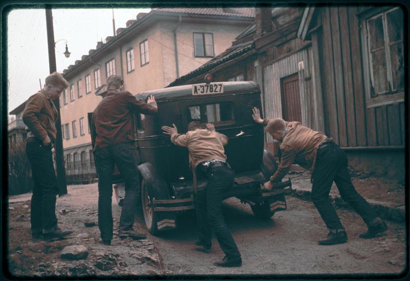 """Odd  Karlsen,  bror  til  Harald  M.  Karlsen,  var  en  av  de  første  på  «Haugen»  som  tok  høyere utdanning.  Her  ser  vi  bilen  som  han  og  hans  klassekamerater  hadde  kjøpt  som  russebil  i 1959. Enerhaugsgjengen  tro  støttende  til  for  å  få  bilen  trygt plassert . Bildet  er  tatt  utenfor  Langleiken 11. Fra  venstre:  Kent Johansen,  Olaf  E  Olsen, Tor  """"Lillern""""  Pedersen  og  Roger  Johansen (Foto/Photo)"""