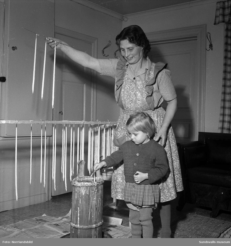 Ljusstöpning på traditionsrik släktgård. Karin Källström och en liten flicka.