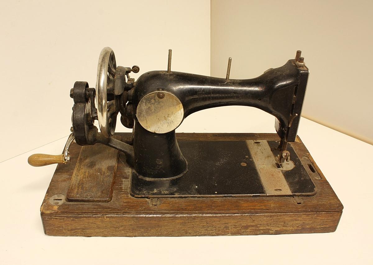 Symaskin typen Singer. Opererast manuellt med sveiv. Eldre modell som er litt mindre i storleik, tung. Ganske slitt.