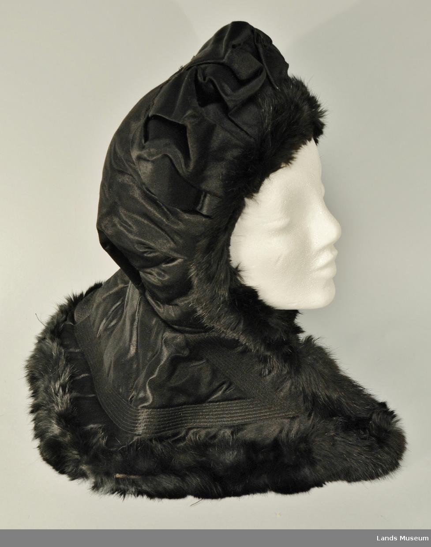 Sydd i silke med kanting i svart skinn, foret med svart bomullssateng, vattert. Det går 8 stikninger langs kanten nedentil, ca 5 cm innanfor kanten og opp til halsen.